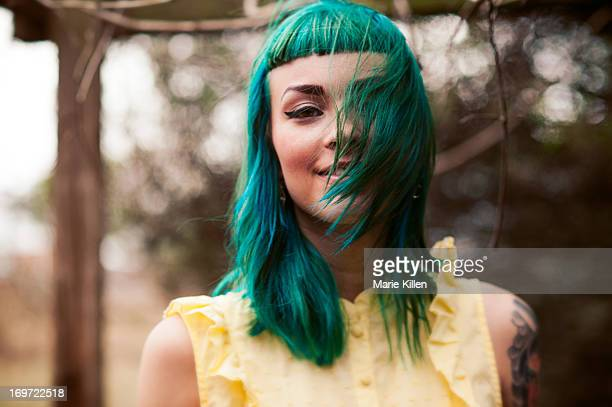 Girl with green hair blowing over her face