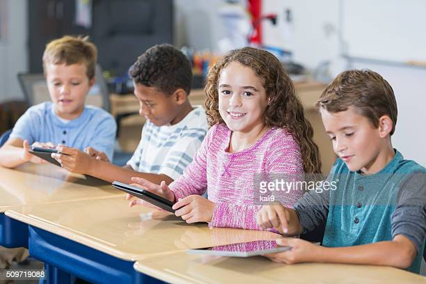 Girl with group of boys in class, digital tablets