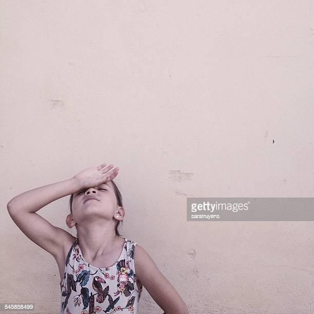 Girl with hand on head on beige background