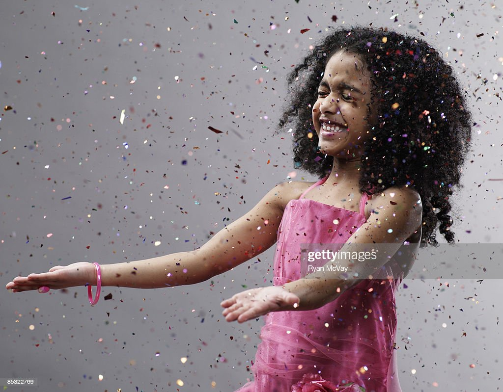 Girl with hands out confetti flying : Stock Photo