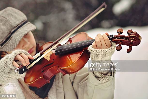 Girl with hat and fingerless gloves playing violin