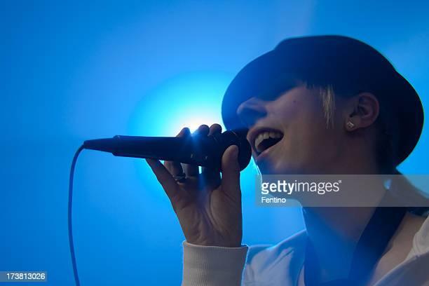 Mädchen mit Hut Singen auf der Bühne blau beleuchtete Hintergrund