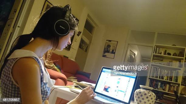 Girl with headphone checks her social media on her laptop