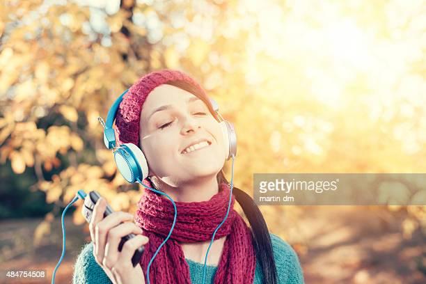Fille avec des écouteurs profitant de la musique dans le parc