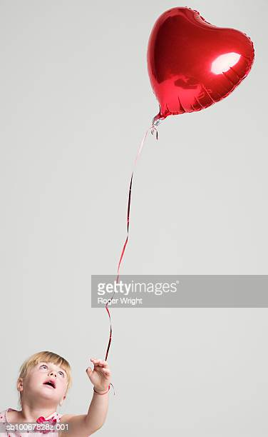 Girl (2-3 years) with heart shaped balloon tied to hand, studio shot