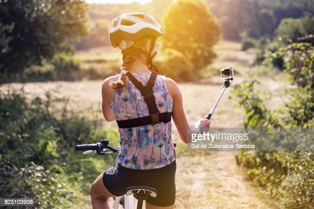 Girl with helmet and a braid taking a selfie on a bicycle in a beautiful sunny day