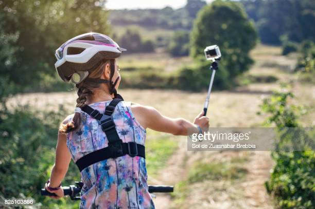 Girl with helmet, braid and sportswear cycling while filming herself with an action camera