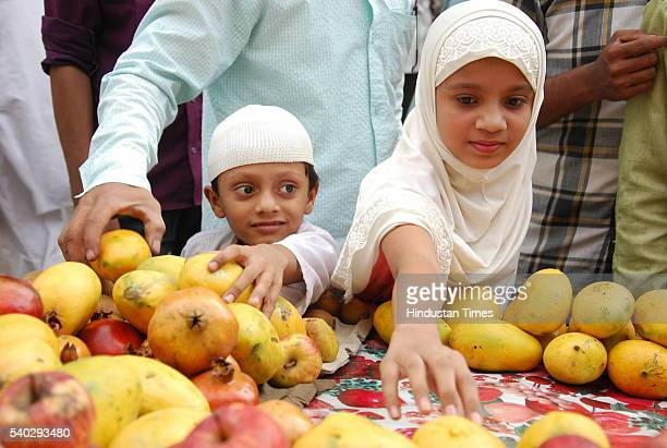 A girl with her brother purchasing mangoes ahead of Iftaar as the Muslim community observes roza during the month of Ramadan on June 14 2016 in...
