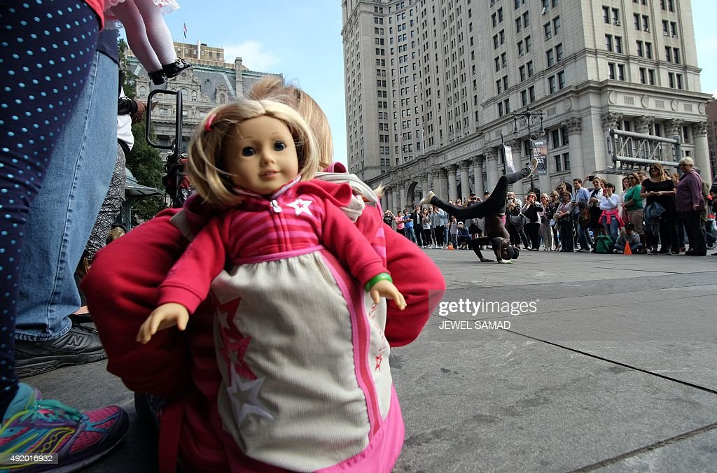 A girl with her doll peeking out of her backpack watches as a street entertainer dances during a road side show in New York on October 9 2015 AFP...