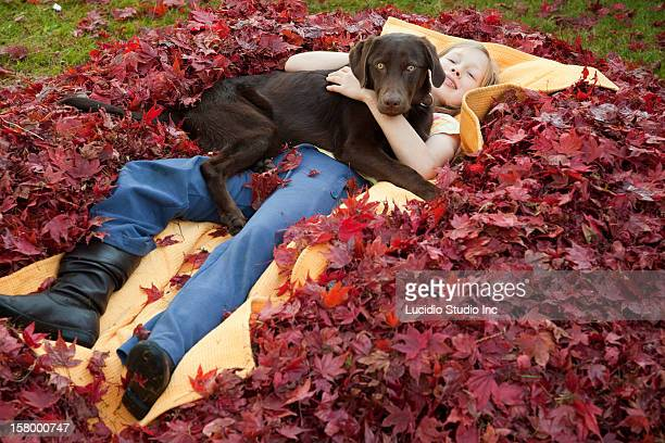 A girl with her Labrador on a pile of maple leaves
