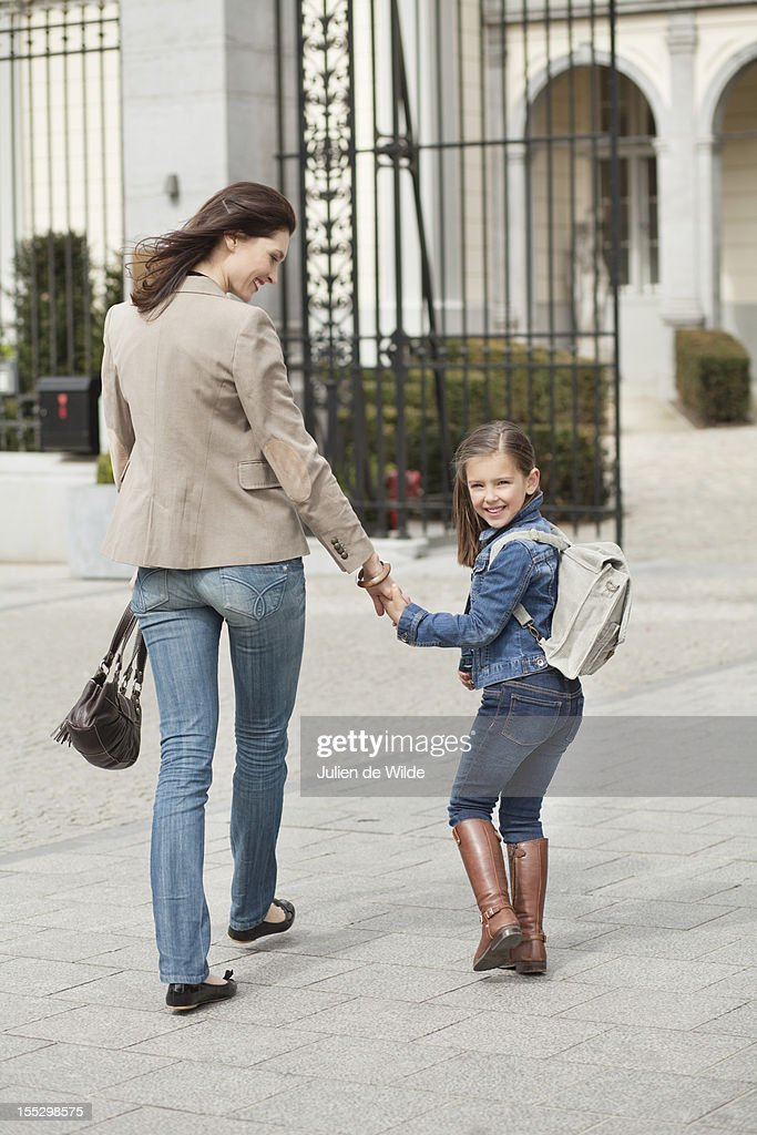 Girl with her mother walking to school : Stock Photo