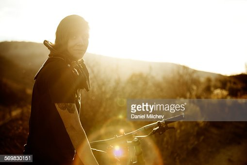 Girl with her mountain bike on a trail at sunset.