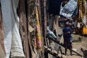 A girl with her neighbours stands on May 28 2014 outside their house in Mathare one of the poorest slums in Nairobi Running water and electricity are...