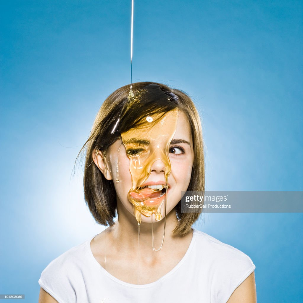 girl with honey pouring on her head : Stock Photo