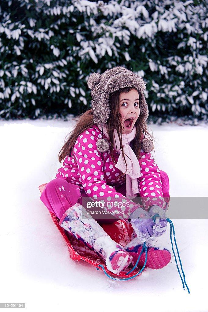 Girl with huge smile playing on sledge : Stock Photo