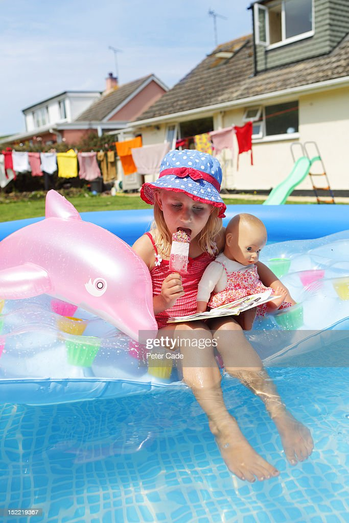 Girl with ice-cream and book in paddling pool : Stock Photo