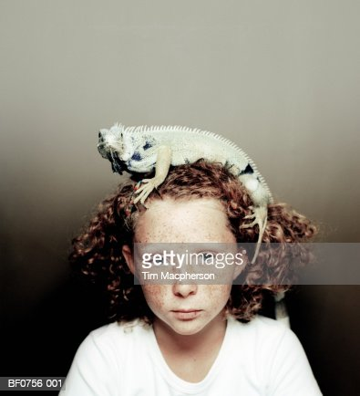 Girl (7-9) with iguana on head