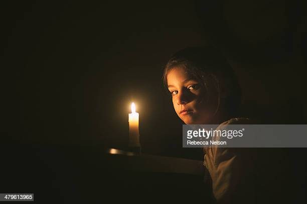 girl, with intense gaze, by candlelight