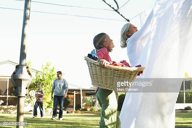 Girl (10-12) with laundry basket looking up at mother hanging out washing