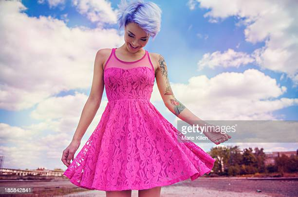 Girl with lavender hair smiling in pink dress