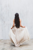 Girl with long black hair in a gentle silk wedding dress
