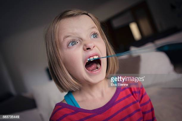 Girl with loose tooth tied to string