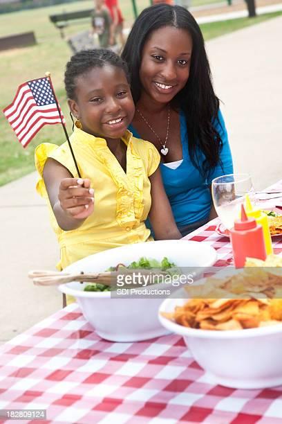 Girl with Mom at Picnic, Waving U.S. Flag