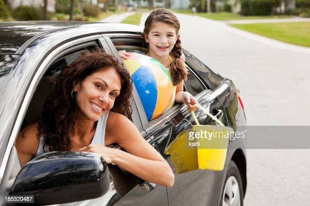 Girl with mother in car driving to beach