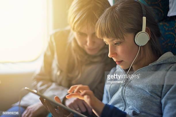 Mädchen mit Mutter Reisen mit Zug und spielen auf einem tablet arbeitet