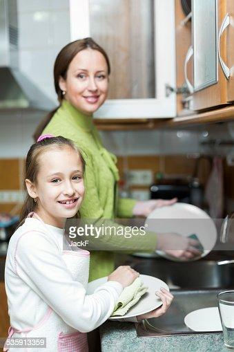 Menina com a mãe de Lavar Louça : Foto de stock
