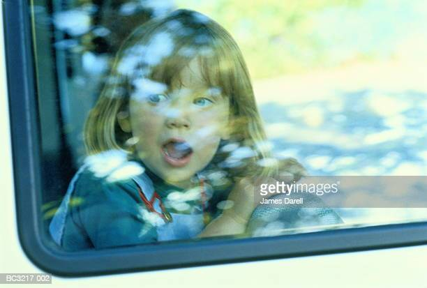 Girl (3-5) with mouth wide open, sitting in car, view through window