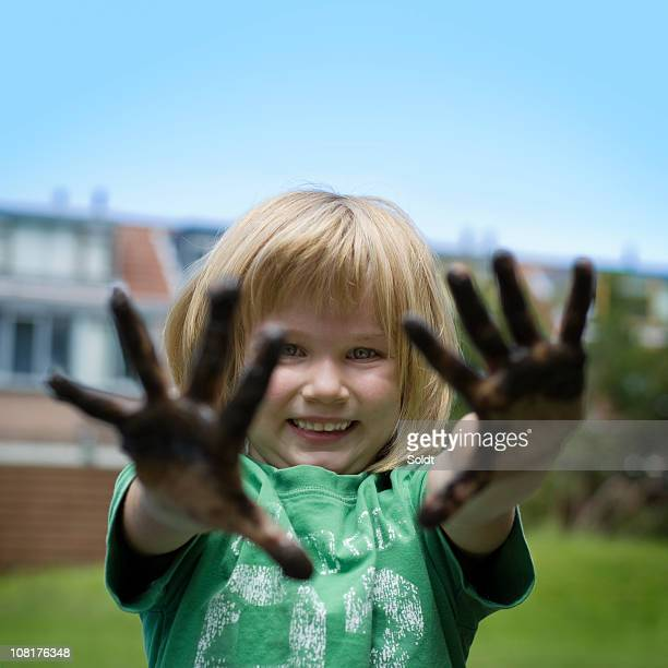 Mädchen mit Schlamm Hände