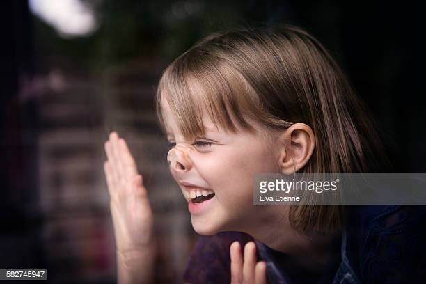 Girl with nose pressed against glass window