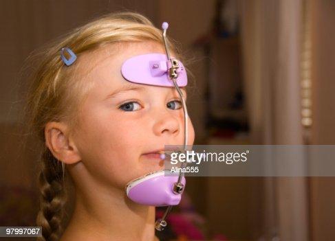 Girl with orthodontics head gear