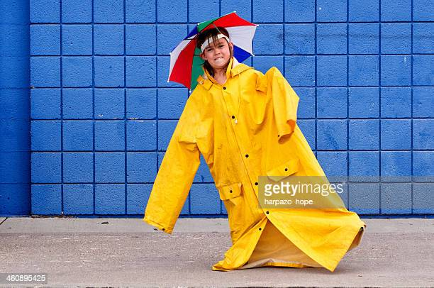Girl with over-sized raincoat and umbrella hat.