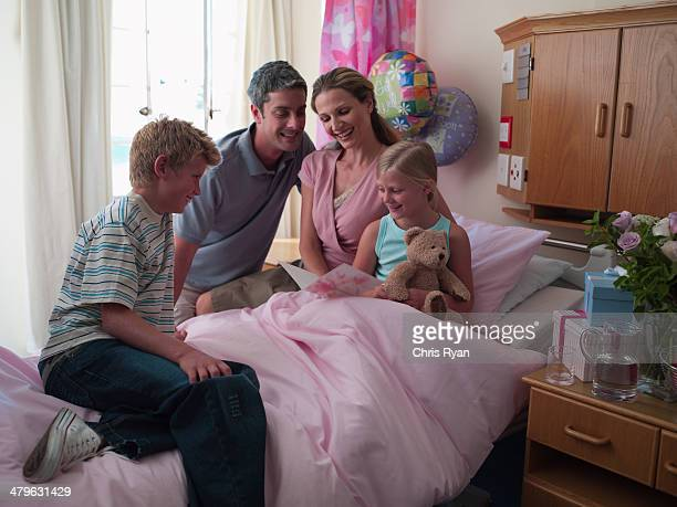 Girl with parents and brother in hospital room