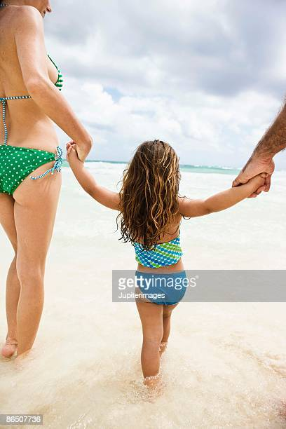 Girl with parents at the beach