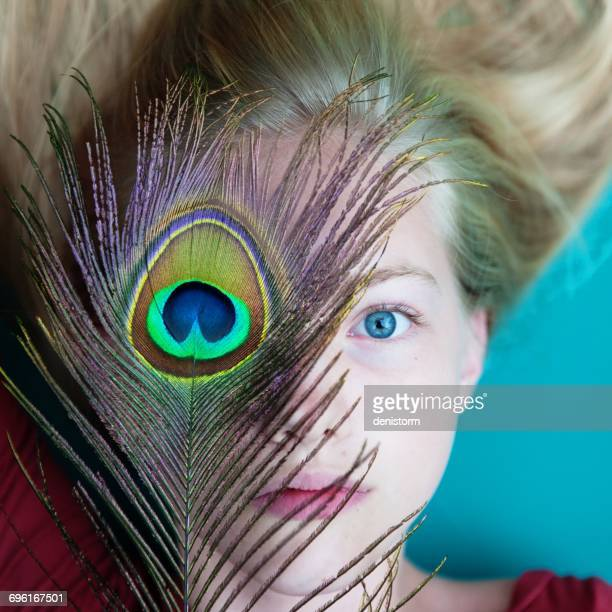 girl with peacock feather over one eye