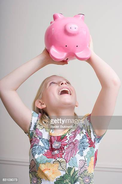 Girl (8-9) shaking piggybank, close-up