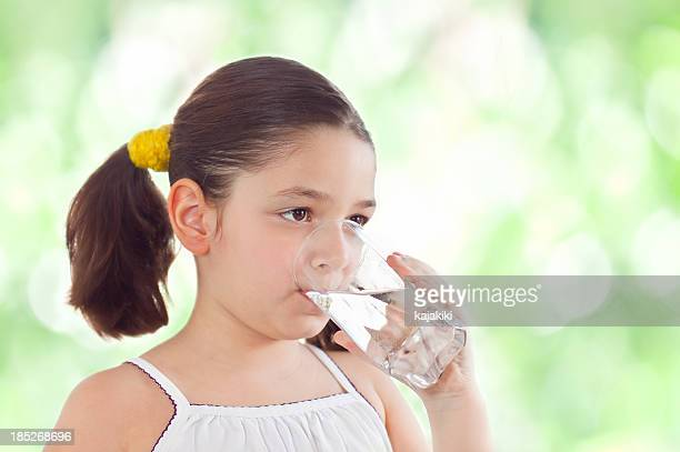 A girl with pigtails drinks a glass of water in the summer