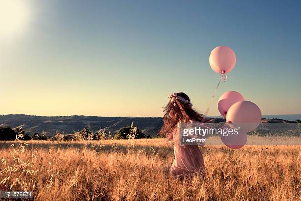 Girl with pink balloons in a field