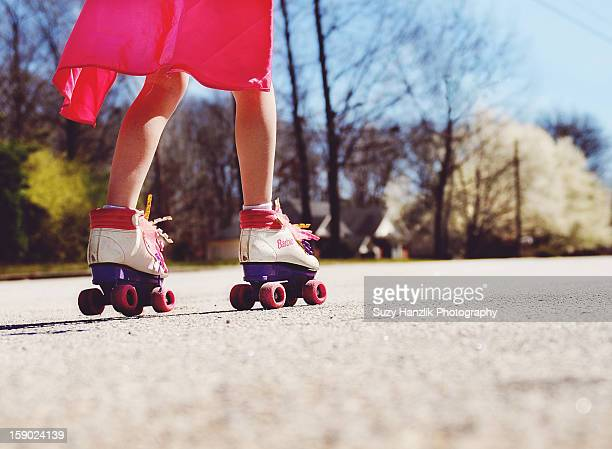 girl with pink cape roller skating in spring