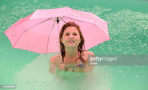 girl with pink umbrella in swimming pool