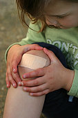 Close up of knee with large plaster and hands cradling it