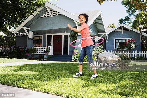 Girl with plastic ring toy on front lawn of house
