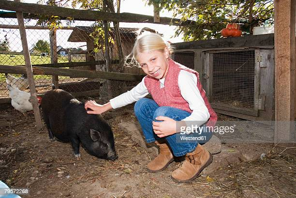 Girl with pot-bellied pig in barn