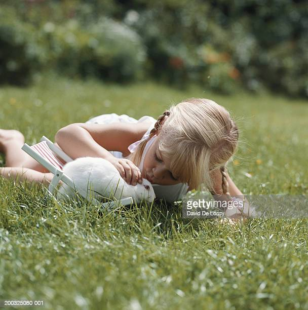 Girl (4-7) with rabbit on deck chair in garden