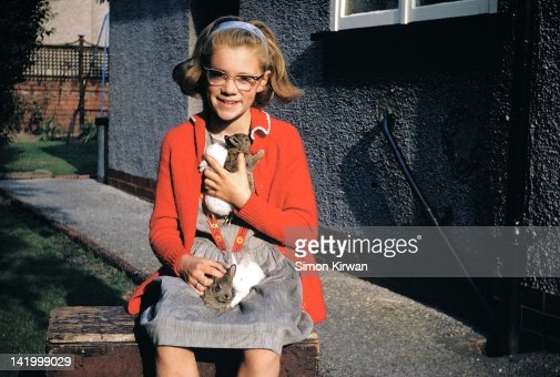 Girl with rabbits by house