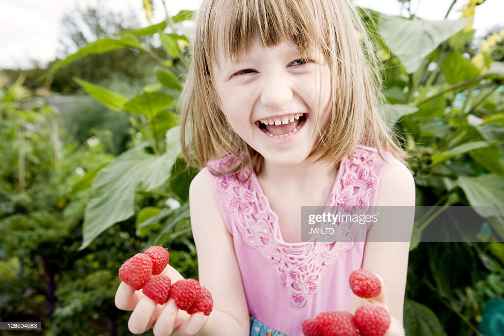 Girl (5-6) with raspberries on fingers, laughing : Stock Photo