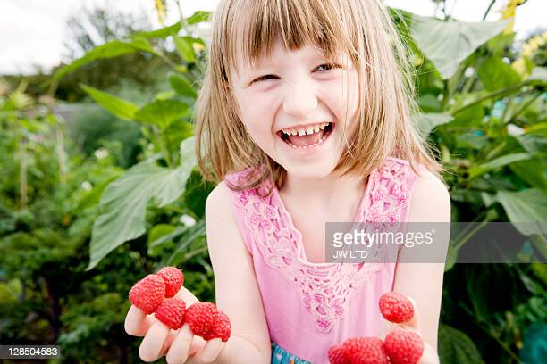 Girl (5-6) with raspberries on fingers, laughing